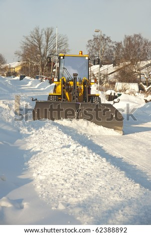 A tractor shoveling snow in a suburban street - stock photo