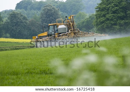 A tractor spraying insecticide on a field of crops - green fields and trees beyond - stock photo