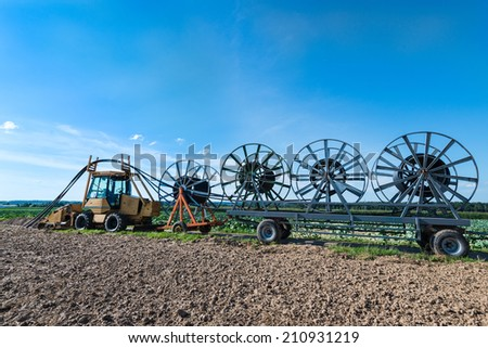 A tractor with trailers is laying fiber optic cables - glass fibers are employed as fiber optic cable for data transmission, increased internet usage demands for a constantly growing infrastructure - stock photo