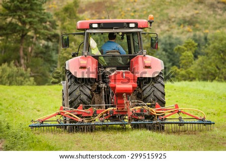 A tractor working on grass with an air powered harrow. - stock photo