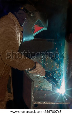 A tradesman welding steel on site at a engineering site at a mine. The sparks from the arc light the gloves and elding shield helmet.