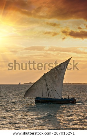 a traditional african dhow with full sail to the wind on a golden background of ocean and warm clouded sky - stock photo
