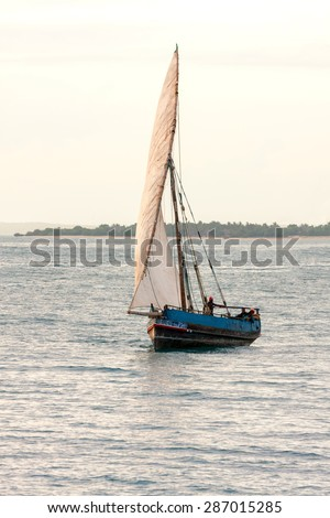 a traditional african nautical vessel the dhow a graceful boat on a calm ocean with full sail in a gentle breeze - stock photo