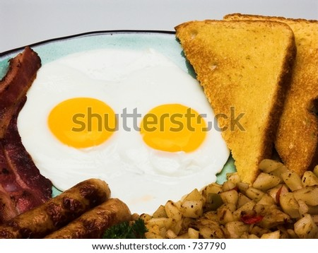 A traditional American breakfast of eggs, bacon, sausage, hash browns, and buttered toast. - stock photo