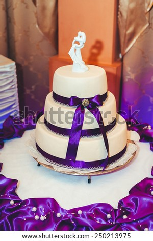 A traditional and decorative wedding cake at wedding reception. three tiered blue and white wedding cake with confectionery roses - stock photo