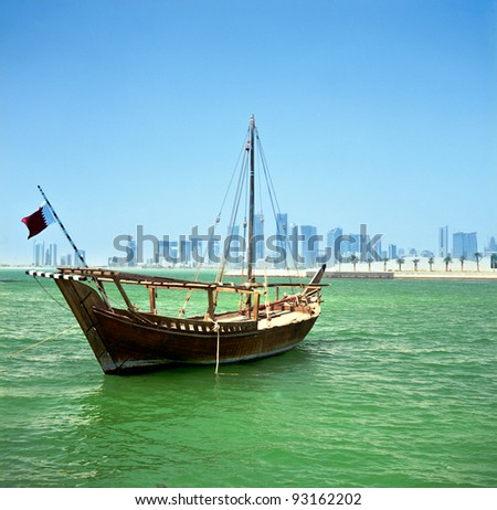 A traditional Arab dhow of the common Shuw'ai type moored in Doha Bay, Qatar, with the city's modern skyline in the background, - stock photo