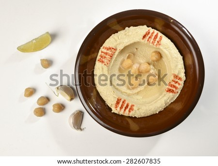 A traditional bowl of Hummus - an arabic chickpea paste, with garlic clove, lemon slice and chickpeas by side. - stock photo