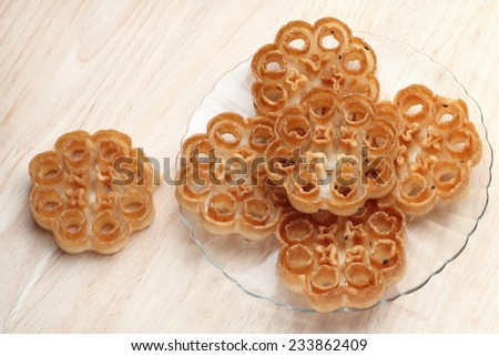 A traditional crunchy snack of Kerala called 'Achappam' on a wooden background - stock photo