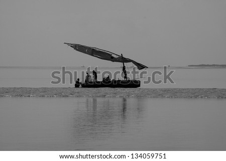 A traditional dhow floats in the lagoons of the Bazaruto Archipelago in Mozambique where fishermen fish in the shallows - stock photo