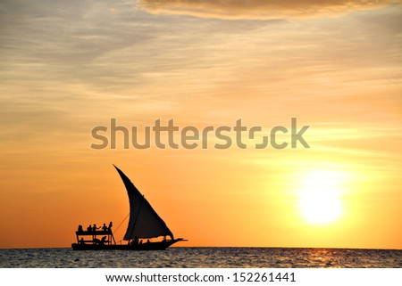 A traditional dhow sails along at sunset in Zanzibar, Tanzania, Africa.