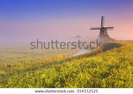A traditional Dutch windmill at sunrise on a beautiful foggy morning.