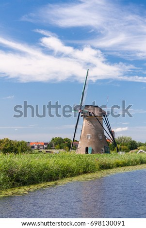 A traditional Dutch windmill framed against a blue sky with white fluffy clouds at Kinderdijk, Netherlands