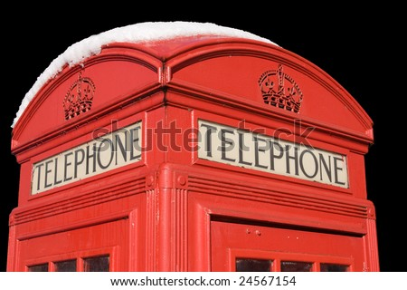 A traditional English telephone box, with snow on the roof, isolated against a black background - stock photo