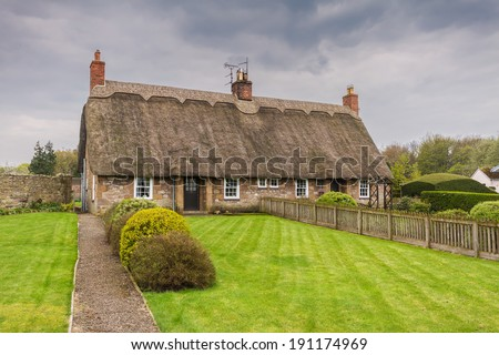 A Traditional English Thatched Roof Cottage   - stock photo