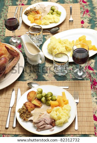 A traditional festive dinner of turkey, roast and boiled potatoes, brussels' sprout, swede, stuffing and gravy - stock photo