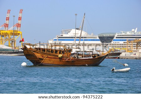 A traditional fishing dhow is anchored in Muscat Harbor, Oman. Cruise ship  is in background. - stock photo