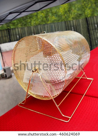 a traditional gold raffle drum full of contest entry ballots on a table top at an