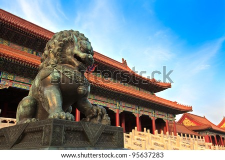 A traditional Imperial guardian lion at the Gate of Supreme Harmony at sunset in Forbidden City. Beijing, China. - stock photo
