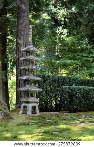 A traditional Japanese lantern in a beautiful green Japanese Garden - stock photo