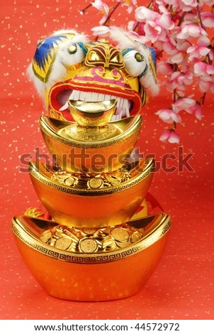 A traditional lion bites a stack of gold ingots,the lion is believed to be able to dispel evil and bring good luck and prosperity in China. - stock photo