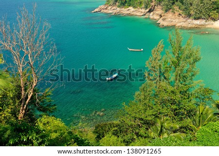 A traditional longtail boat floats in perfect crystal clear emerald blue water. Phuket, thailand - stock photo