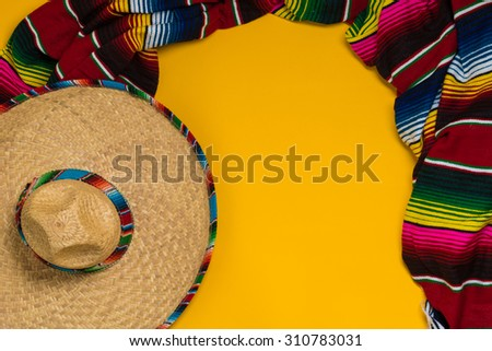 A traditional Mexican Sombrero and serape blanket on a yellow background with copy space - stock photo