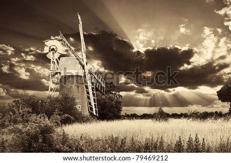 a traditional norfolk broads windmill with a spectacular sky and a sepia tone to give a vintage appearance
