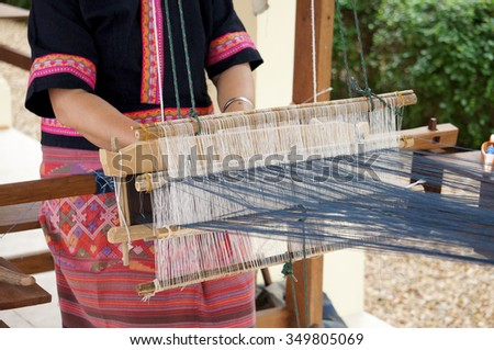 A traditional of thai woman hand weaving loom being used to make cloth  - stock photo