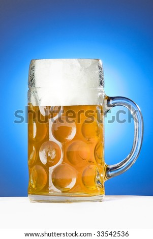 A traditional Oktoberfest (Wiesn) beer on a blue background. - stock photo