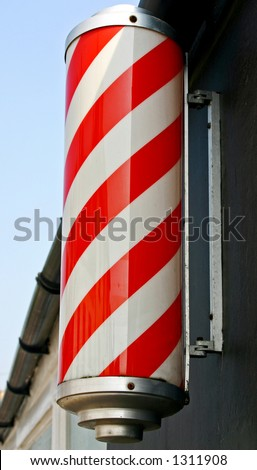 A traditional red and white striped barber's pole. - stock photo