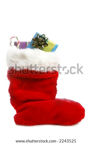 A traditional red Christmas stocking over white with gifts - stock photo