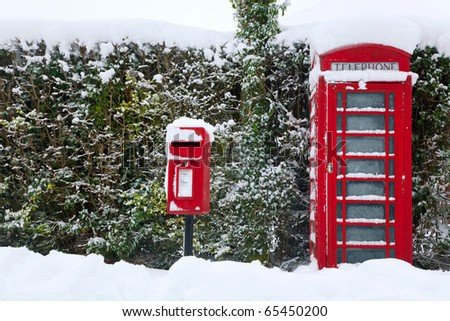 A traditional red English public phone and post box after a heavy snow fall. - stock photo
