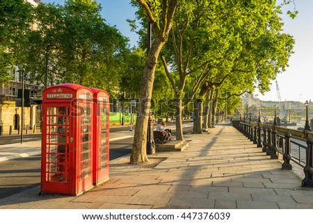 A traditional red phone booth in London at sunny morning - stock photo