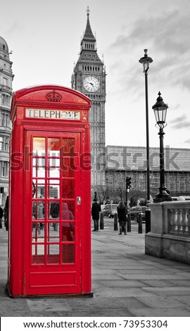 A  traditional red phone booth in London with the Big Ben in a black and white background - stock photo