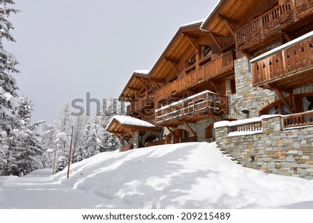 A traditional ski resort hotel, chalet style, built out of stone and wood along a path through the trees in the snow. - stock photo