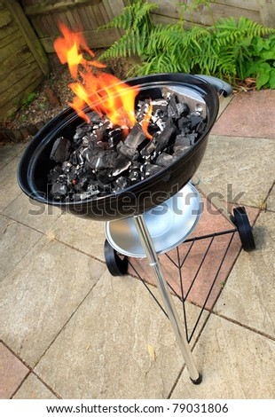 a traditional style bbq with flames coming through the grill - stock photo