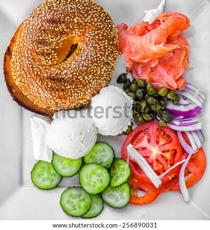 A traditional, toasted, sesame seed bagel with Norwegian salmon, two big balls of Philadelphia cream cheese, marinated capers, sliced cucumber, tomatoes and thin rings of red onion. - stock photo