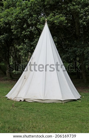 A Traditional White Canvas Bell Shaped Camping Tent. - stock photo