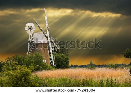 a traditional windmill in the norfolk broads, england with spectacular sun beams following a storm in the background - stock photo