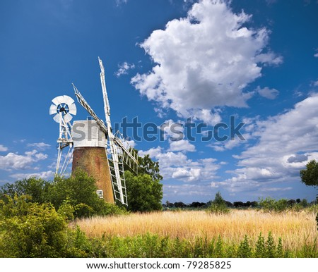 a traditional windmill on a sunny day in the norfolk broads of england with a bright blue sky and white clouds beyond