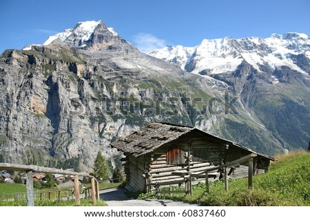 A traditional wooden hut under the foot of the Alps in Switzerland - stock photo