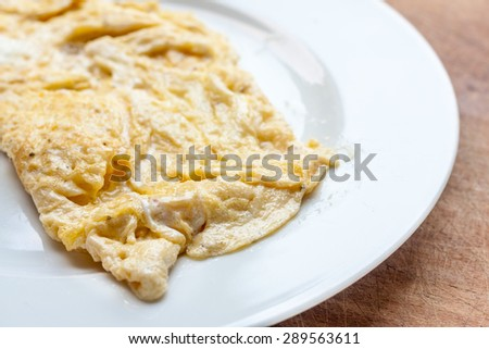 A traditionally cooked french omelette on a white plate - stock photo