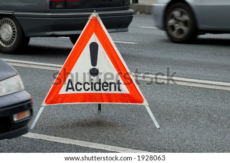 A traffic accident sign in the middle of a busy road, cars passing on either side. Motion blur on the cars.