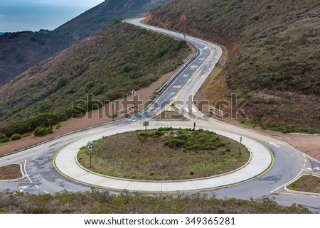 A traffic circle in the hills of Marin County with a road leading up the hill - stock photo