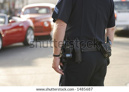 A traffic cops watches a busy intersection.