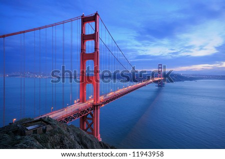 A traffic flows along the glowing Golden Gate Bridge behind ruins of old fortification