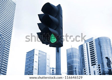 A traffic light shows green with a curving lamp post framing the background office tower. Focus is on the lights. Kuala Lumpur - stock photo