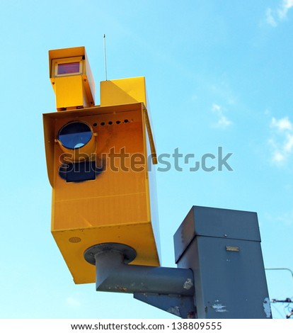 A traffic speed monitoring camera, against a bright blue sky. - stock photo