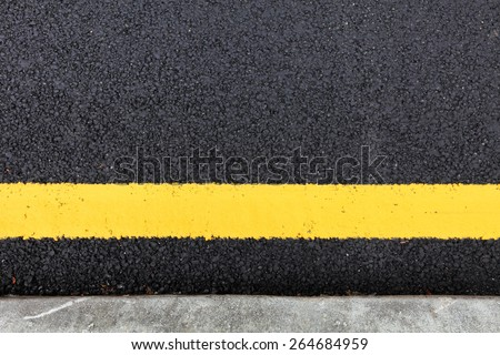 A traffic yellow line painted on a tarmac road by a side kerb.  - stock photo