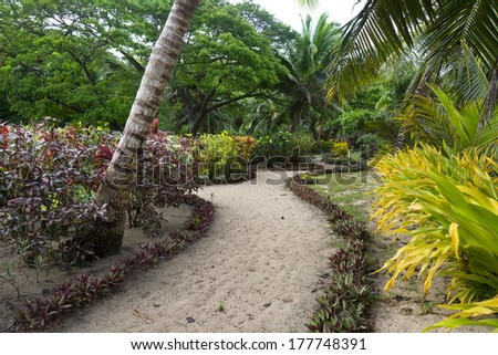 A trail through a lush south pacific resort garden shows the detail given to elegance. - stock photo